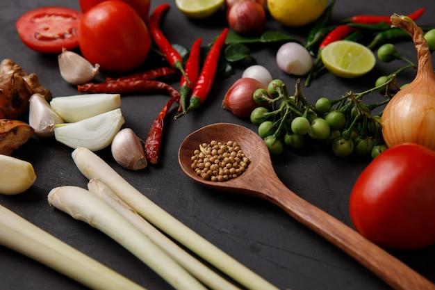 Diverses herbes et ingrédients à cuisiner sur un fond sombre.