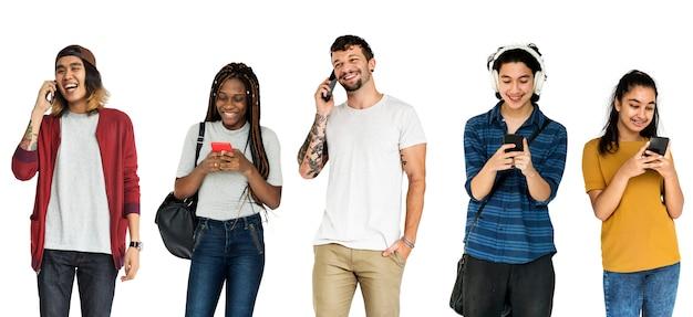Diverses jeunes adultes utilisant des appareils mobiles studio isolé