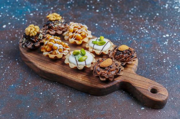 Diverses mini tartelettes maison aux noix et crème au chocolat.