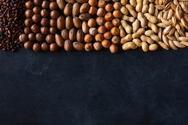 Diverses noix sur la table en pierre noire. vue de dessus avec espace de copie