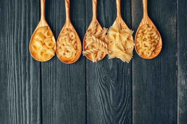Diverses pâtes sur des cuillères sur fond en bois