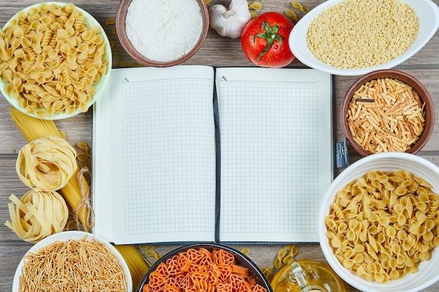 Diverses pâtes non cuites avec cahier et légumes sur une table en bois.