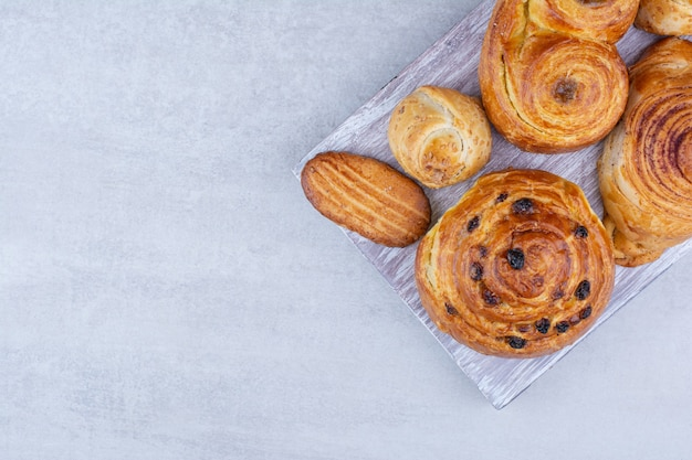 Diverses pâtisseries et petits pains avec des biscuits sur planche de bois.