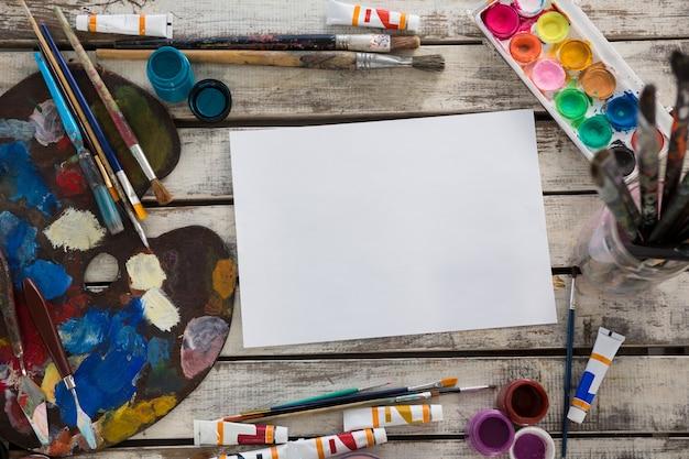 Diverses peintures à l'aquarelle, palette et pinceaux sur une surface en bois