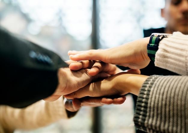 Diverses personnes empilant les mains ensemble