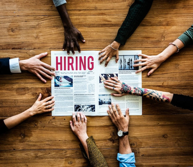 Diverses personnes se donnent la main pour embaucher une annonce dans un journal