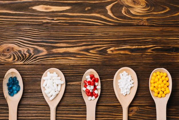 Diverses pilules sur une cuillère en bois