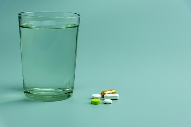 Diverses pilules et verre d'eau sur fond gris