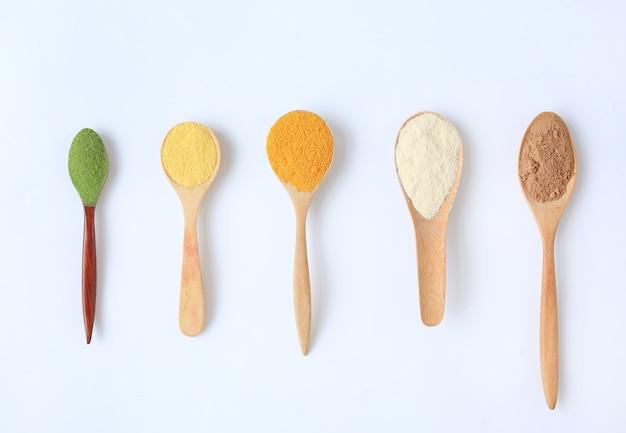 Diverses poudre colorée dans différentes cuillères en bois isolées.
