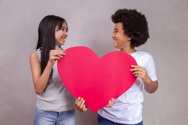 La diversité. enfant japonais et noir tenant une carte en forme de coeur sur fond gris avec un espace pour le texte. la journée des enfants
