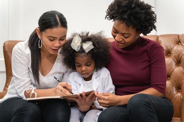Diversité lgbt couple de lesbiennes. couple de lesbiennes avec sa fille africaine en riant et dessinant une photo