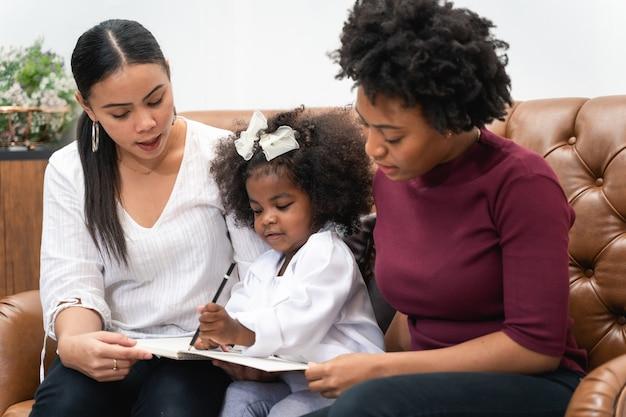 Diversité lgbt couple de lesbiennes moments de bonheur avec sa fille africaine en riant et en dessinant une photo