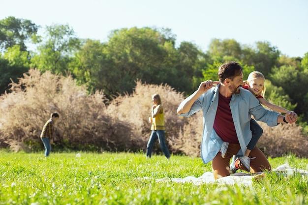 Divertissant. papa barbu inspiré s'amusant avec sa fille et sa mère jouant avec leur fils en arrière-plan