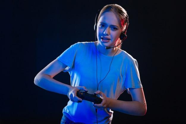 Divertissement agréable. belle jolie femme portant des écouteurs tout en jouant à des jeux vidéo