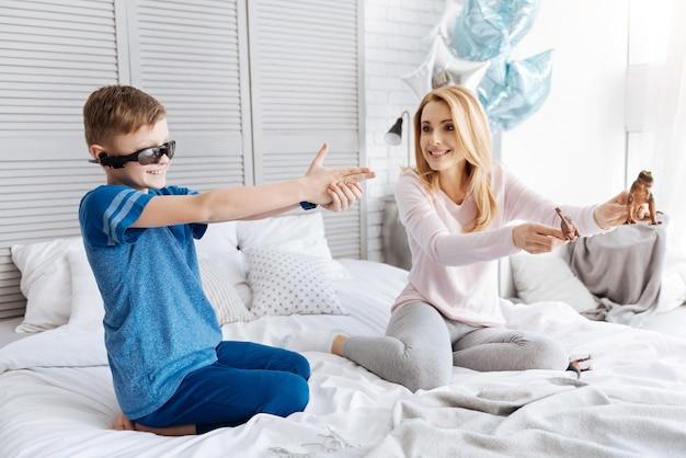 Divertissement intéressant. joyeuse heureuse jeune mère assise sur le lit et tenant des jouets tout en jouant avec son fils