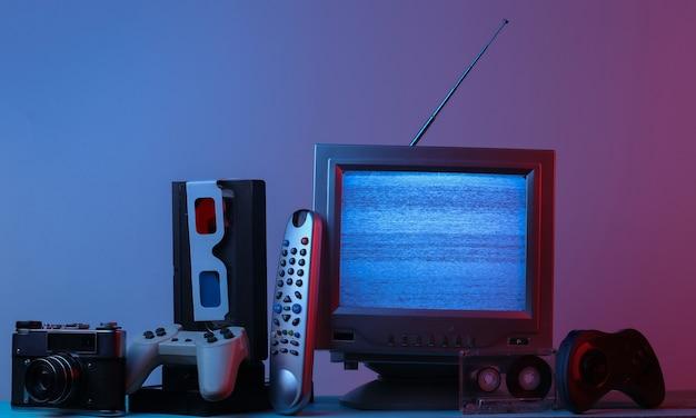 Divertissement multimédia rétro des années 80 antenne récepteur de télévision à l'ancienne lunettes anaglyphes horloge audio et vidéo cassette manette de jeu caméra à distance en lumière dégradé bleu rose vague rétro