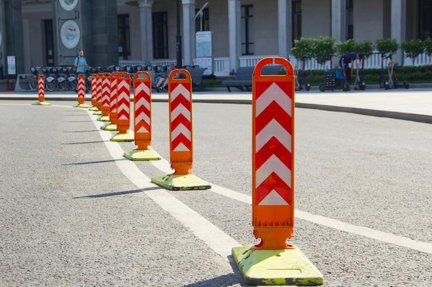 Diviseurs de route orange. ligne courbe de poteaux de séparation sur la double ligne de marquage au sol