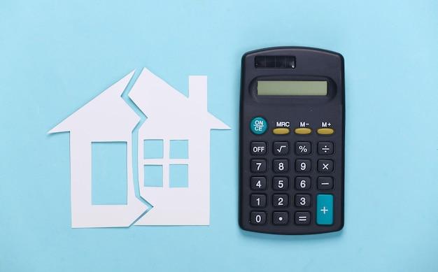 Divorce, concept de division de propriété. maison de papier fendue et calculatrice sur bleu