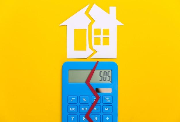 Divorce, concept de division de propriété. maison de papier fendue et calculatrice sur jaune