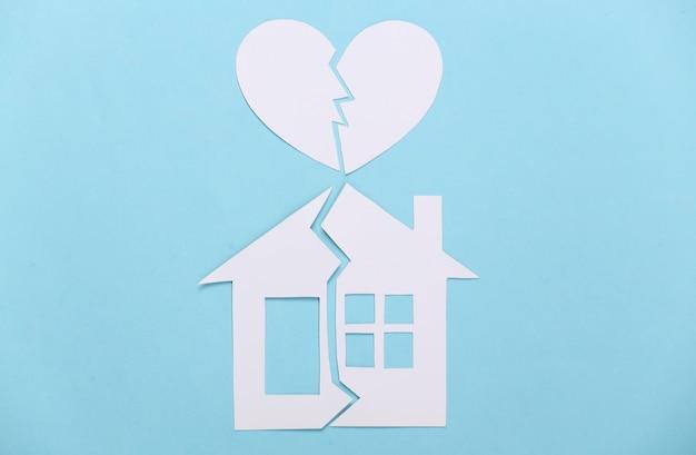 Divorce, concept de division de propriété. maison de papier fendue et coeur brisé sur bleu