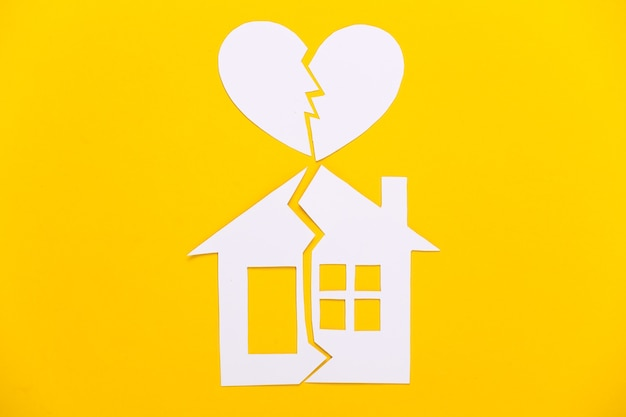 Divorce, concept de division de propriété. maison de papier fendue et coeur brisé sur jaune