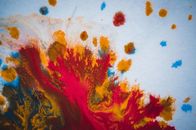Divorces et gouttes de peinture rouge, orange, jaune, bleu abstrait flou sur fond de papier blanc surface plane macro close-up avec effet de tonification du filtre
