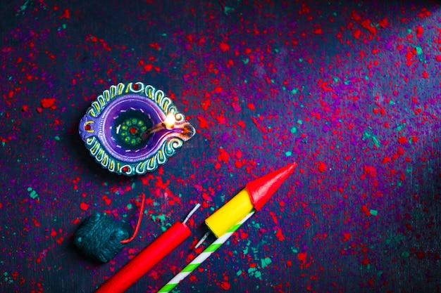 Diwali diya avec fire crackers sur fond de rangoli