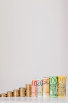 Dix, vingt, cinquante, cent, deux cent pièces et billets de billets roulés en euros sur fond blanc. histogramme de l'euro. concept de croissance monétaire, épargne.