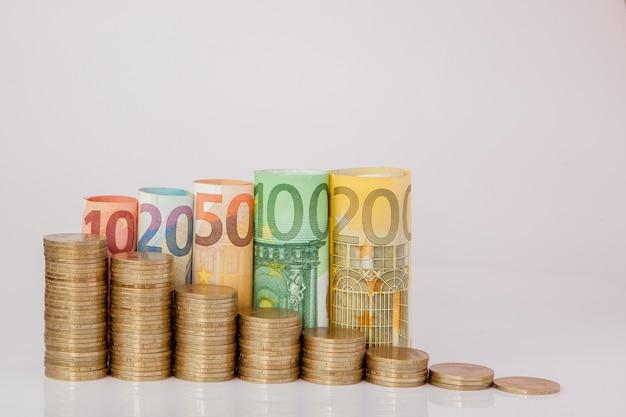 Dix, vingt, cinquante, cent, deux cents et pièces en euros billets roulés billets de banque sur fond blanc. histogramme de l'euro. concept de croissance monétaire, d'épargne.