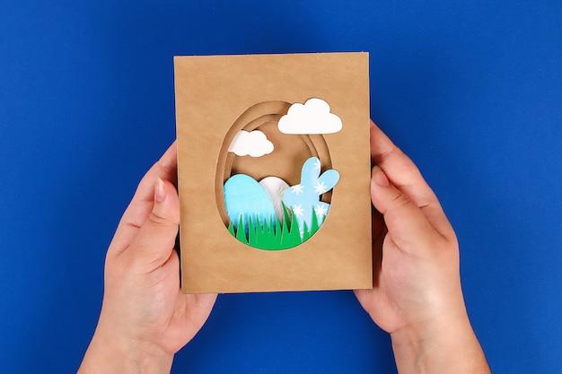 Diy cartes de pâques en papier. volume des cartes de voeux avec un lapin, oeuf sur fond bleu. 3d.