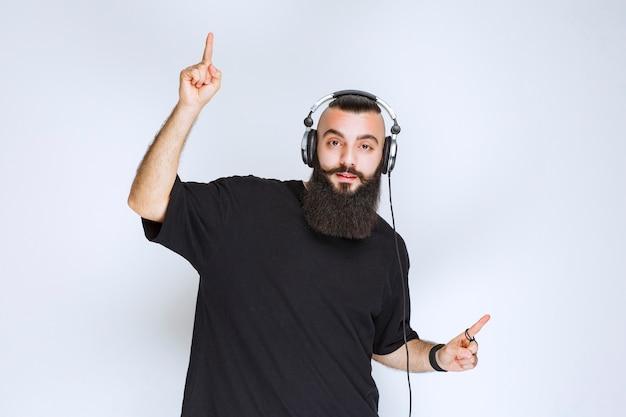 Dj avec barbe portant des écouteurs et pointant vers le haut.
