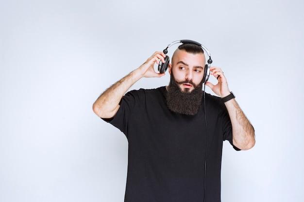 Dj avec barbe portant ou enlevant les écouteurs.
