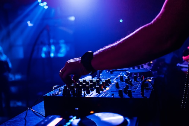 Dj en boîte de nuit gère et mixe la musique sur une table de mixage