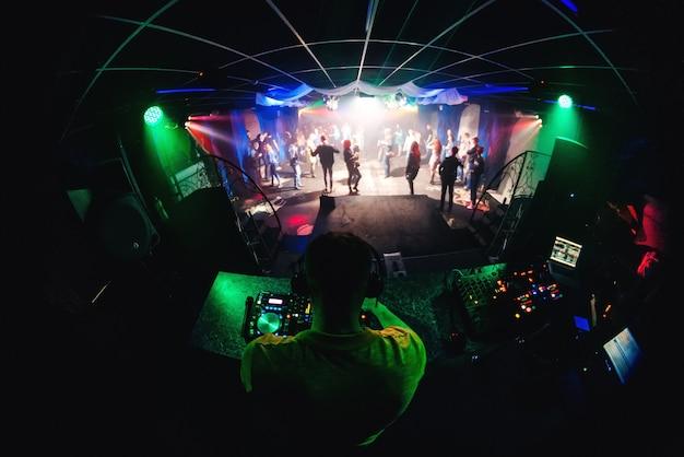Dj en boîte de nuit mixant de la musique sur une table de mixage avec des écouteurs et des gens dansant sur la piste de danse
