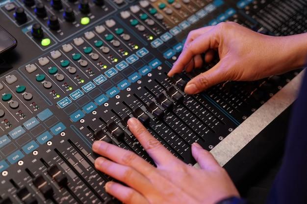 Dj contrôle le contrôleur sonore et joue de la musique edm mixte dans la discothèque de concert lors d'une fête.