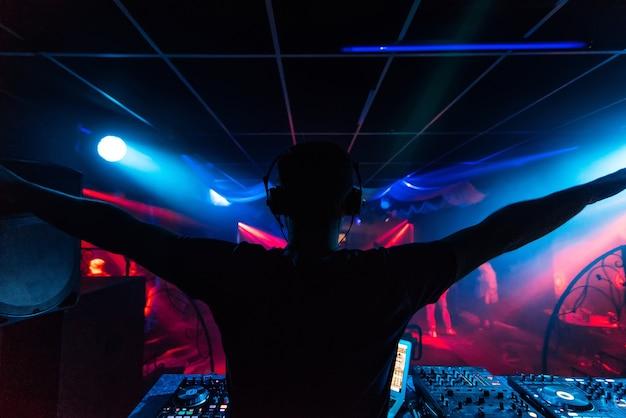 Dj dans les écouteurs agitant ses bras à la silhouette d'une boîte de nuit de fête avec une lumière colorée