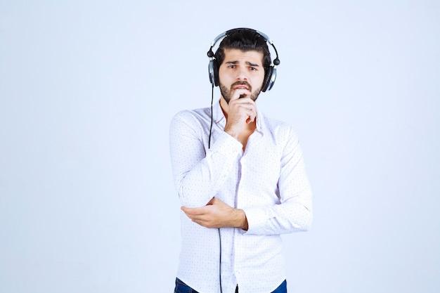 Dj avec des écouteurs a l'air confus et réfléchi