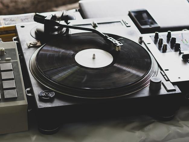Dj jouant de la musique lors d'une soirée hip hop. platine analogique, dj utilise une platine et une table de mixage pour le scratch.