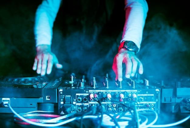 Dj jouant de la musique à la table de mixage en boîte de nuit