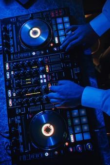 Dj joue sur un mélangeur de musique dans une boîte de nuit