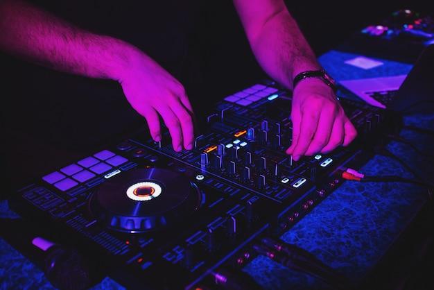 Dj joue de la musique avec ses mains sur une console de mixage