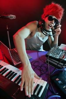 Dj avec lumière colorée et équipement de mixage de musique