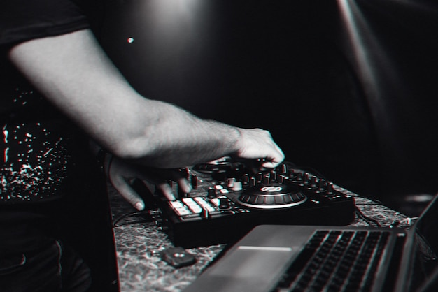 Dj mains jouant de la musique contemporaine électronique sur la console de mixage lors d'un concert dans une discothèque