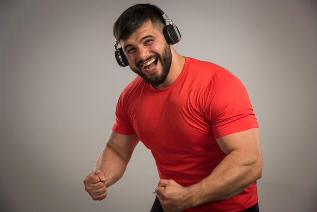 Dj masculin en chemise rouge portant des écouteurs et dansant.