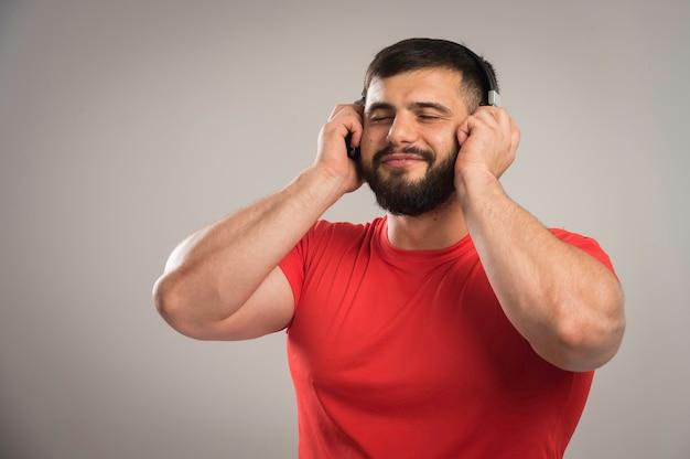 Dj masculin en chemise rouge portant des écouteurs et écoutant de la musique.