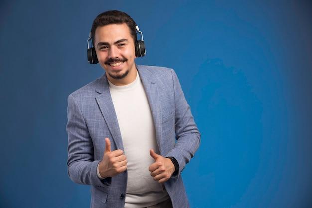 Dj masculin en costume gris portant des écouteurs et dansant.