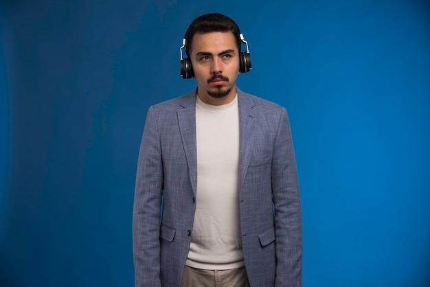 Dj masculin en costume gris portant des écouteurs et se dresse sans émotion.