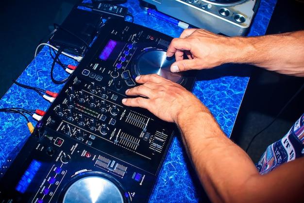 Un dj mélange du matériel de musique professionnel pour une discothèque en boîte de nuit