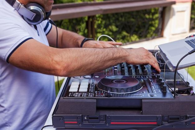 Dj met la main sur l'équipement. table de mixage dj console de contrôle à deux mains en concert