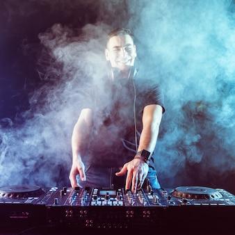 Dj mixage de musique sur table de mixage sur fond sombre